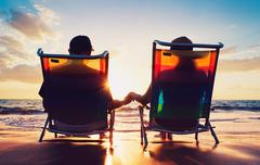 senior couple of old man and woman sitting on the beach watching sunset - stock photo