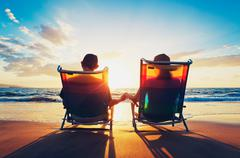 Senior couple of old man and woman sitting on the beach watching sunset Stock Photos