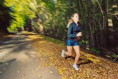 Woman running outdoors with motion blur Stock Photos