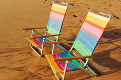 Hawaiian vacation sunset concept, two beach chairs at sunset Stock Photos