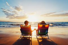 Happy romantic couple enjoying beautiful sunset at the beach Stock Photos