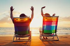 happy romantic couple enjoying beautiful sunset at the beach - stock photo