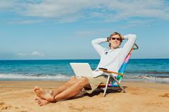 Young attractive man relaxing at the beach with laptop computer Stock Photos
