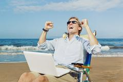Young attractive man celebrating success, working on computer at the beach Stock Photos