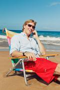business man calling by cell phone at the beach - stock photo