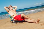Portrait of calm young man relaxing on the beach Stock Photos