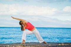 beautiful yoga woman practicing yoga by the ocean - stock photo