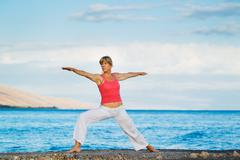 Beautiful yoga woman practicing yoga by the ocean Stock Photos