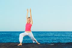 Stock Photo of beautiful yoga woman practicing yoga by the ocean