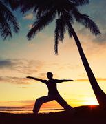 Silhouette of a beautiful yoga woman at sunset Stock Photos