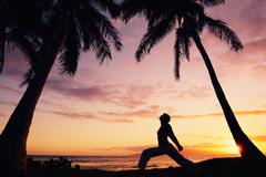 silhouette of a beautiful yoga woman at sunset - stock photo