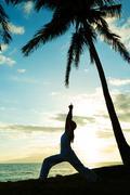 Woman doing yoga at sunset Stock Photos