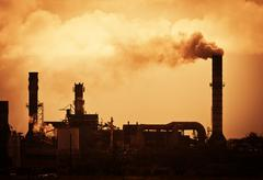 global warming smoke rising from factory - stock photo