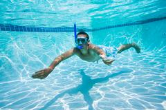 Stock Photo of young man swimming under water in pool