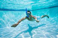 Young man swimming under water in pool Stock Photos