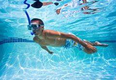 Young man swimming in pool underwater Stock Photos