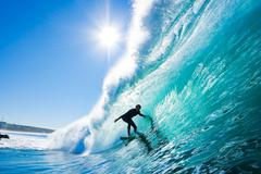 Surfer on blue ocean wave Stock Photos