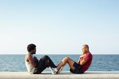 Two men exercising abs near the sea Stock Photos