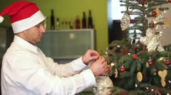 Young man decorate christmas tree Stock Footage