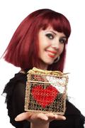 Stock Photo of happy girl smiling with heart packed in a golden gift box