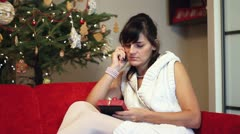 Happy woman sitting with mobilephone near christmas tree Stock Footage