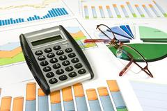 colorful  charts, calculator and glasses - stock photo