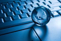 transparent globe on a laptop  keyboard - stock photo