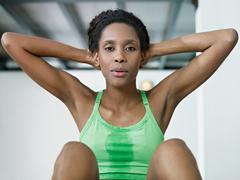 African woman doing series of crunch in gym Stock Photos