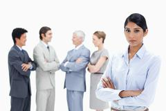 Close-up of a multicultural business team talking and a serious woman in Stock Photos