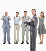 Stock Photo of Blonde woman with business people approving behind her