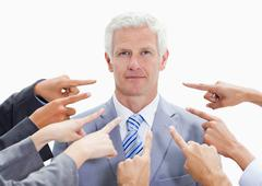 Serious businessman with fingers being pointed at him Stock Photos