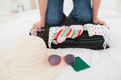 Woman kneeling on suitcase in an attempt to make things fit Stock Photos