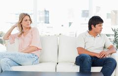 Man turned away looking angry, while the woman looks over to him looking upset Stock Photos