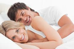 Man and woman happy in bed, the man's arm wrapped around the woman Stock Photos