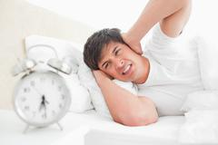Man covering his ears as his alarm clock rings loudly Stock Photos
