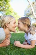 A mother and daughter rub noses while lying on the grass Stock Photos