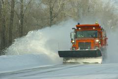 Orange snow plows clearing highway Stock Photos