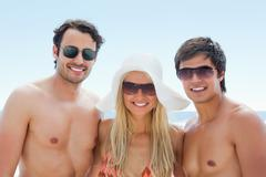 Three freinds smiling as they wear sunglasses - stock photo