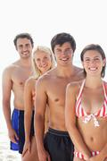 Woman in a bikini smiling happily as she stands in front of her three friends Stock Photos