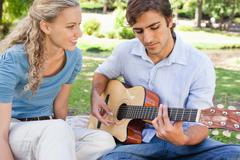 Man playing a song on the guitar for his girlfriend - stock photo
