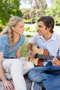 Man in the park playing a song for his girlfriend - stock photo