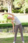 Sportswoman in the park doing her warm-up Stock Photos