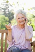 Woman smiling while making a call and performing a hand gesture Stock Photos