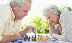 Man and a woman playing chess Stock Photos