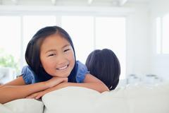 Smiling girl facing the camera as her sister faces away Stock Photos