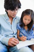A father and daughter studying the school work Stock Photos