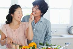 A husband gladly accepts his wife's offer of a red pepper slice Stock Photos