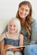 The two girls smile as they look forward with a tablet pc in front of the girl Stock Photos