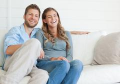 Mies ja nainen istuvat sohvalla yhdessä, koska ne nauravat tv-ohjelman Kuvituskuvat