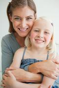 Stock Photo of Close up of a smiling mother and daughter as they sit on the couch
